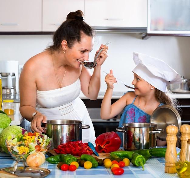 Vrolijk gelukkig meisje die moeder helpen te koken
