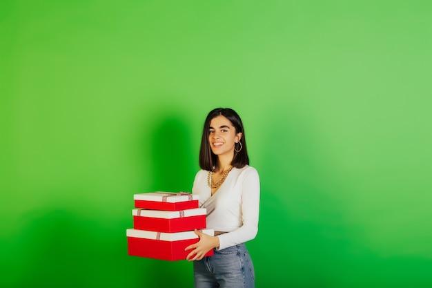 Vrolijk, gelukkig meisje houdt geschenkdozen, opgewonden glimlachend. ze viert verjaardag en poseren op groen oppervlak.
