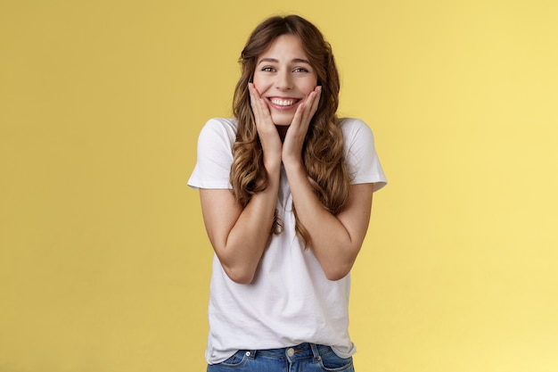 Vrolijk gelukkig vrolijk jong meisje krijgt een ongelooflijke kans om in het buitenland te studeren student juichen vieren verbluffend nieuws aanraking wangen blozen vreugde geluk glimlachend in het algemeen gele achtergrond.