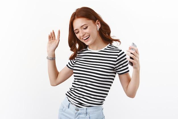 Vrolijk gembermeisje in gestreept t-shirt met geweldige geluidskwaliteit, nieuwe draadloze oortelefoons gekocht, smartphone vasthouden, handen zorgeloos opsteken, dansen en glimlachen, muziek luisteren, witte muur