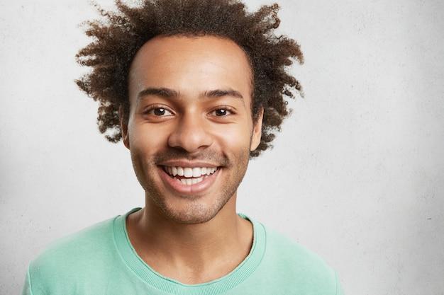 Vrolijk gemengd ras mannetje met borstelharen, borstelig kapsel en witte perfecte tanden, heeft een goed humeur