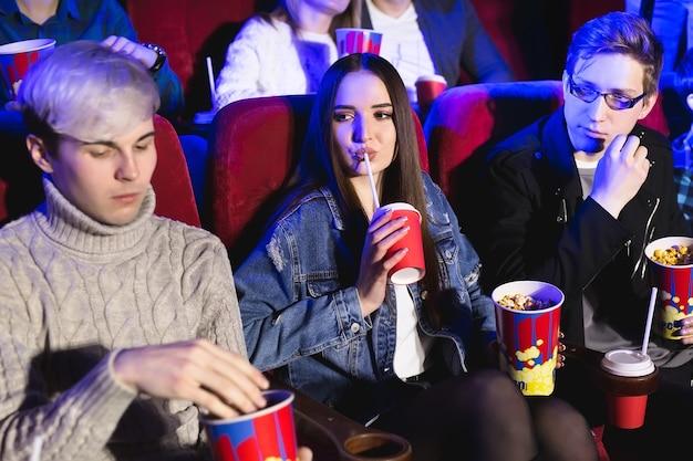 Vrolijk gezelschap in de bioscoop een vrouw drinkt uit een glas, een man eet popcorn