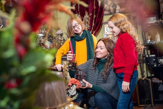 Vrolijk gezin, moeder en kinderen op zoek naar woondecoratie en vakantiegeschenken in huishoudelijke winkel