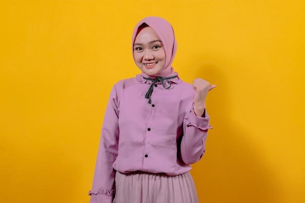 Vrolijk glimlachen en er gelukkig uitzien met het dragen van hijab, zorgeloos voelen en positief wijzend met duimen omhoog