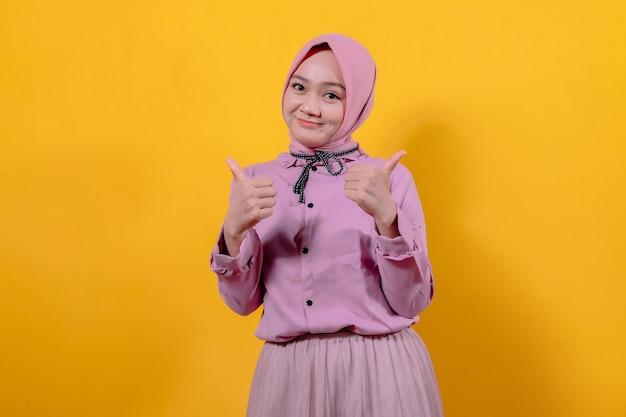 Vrolijk glimlachen en er gelukkig uitzien met hijab, zorgeloos en positief voelen met beide duimen omhoog