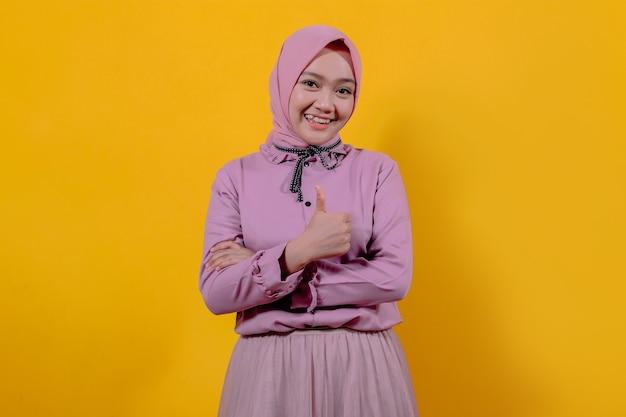 Vrolijk glimlachen en er gelukkig uitzien met hijab, zorgeloos en positief voelen met duimen omhoog