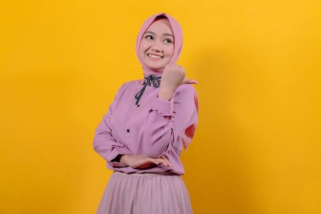 Vrolijk glimlachen en er gelukkig uitzien met hijab, zorgeloos en positief wijzend met duimen omhoog