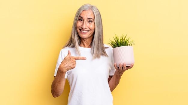 Vrolijk glimlachen, zich gelukkig voelen en naar de zijkant en naar boven wijzen, een object in de kopieerruimte tonen met een decoratieve plant