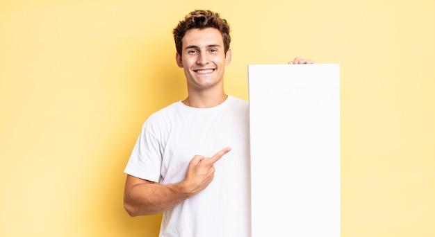 Vrolijk glimlachen, zich gelukkig voelen en naar de zijkant en naar boven wijzen, waarbij het object in de kopieerruimte wordt weergegeven. leeg canvasconcept