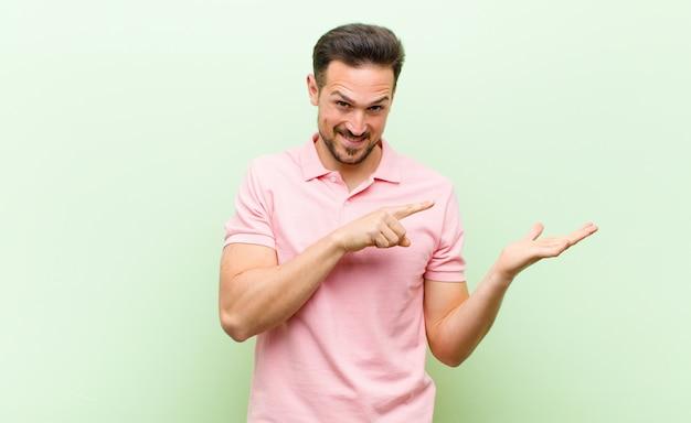 Vrolijk glimlachend en wijzend om de ruimte op de palm aan de zijkant te kopiëren, een object te tonen of te adverteren