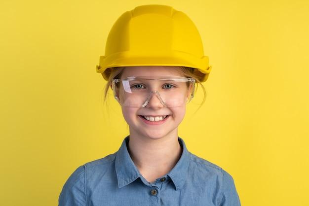 Vrolijk, glimlachend kind in een helm en bouwbril op een gele muur