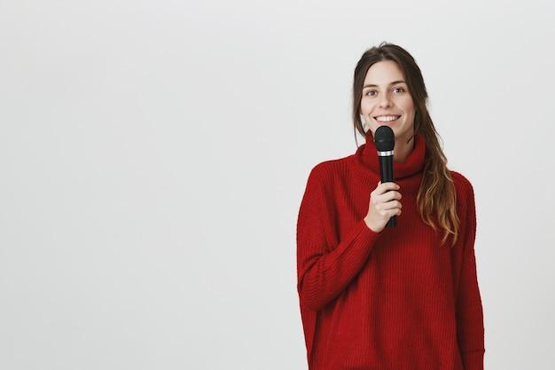 Vrolijk glimlachend meisje dat in microfoon spreekt