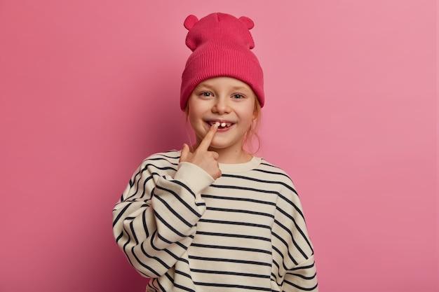 Vrolijk grappig meisje wijst naar haar tanden, geeft om mondhygiëne, gekleed in modieuze kleding, heeft een gezonde huid, pronkt met volwassen tand aan vrienden op de speelplaats, geïsoleerd op roze pastel muur