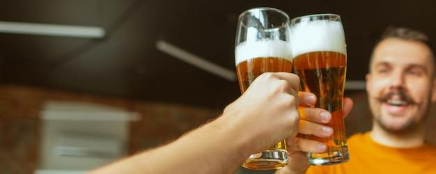 Vrolijk. handen van vrienden, collega's tijdens bier drinken, plezier maken, rammelende flessen, glazen samen.