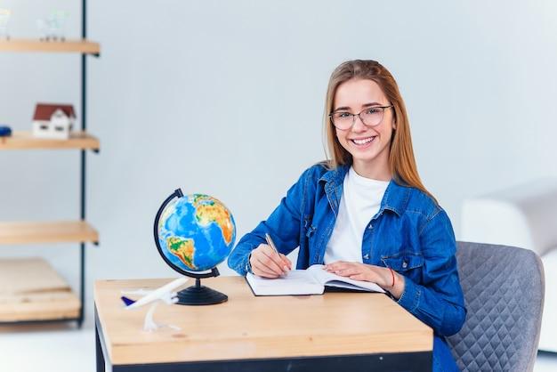 Vrolijk hipstermeisje die als journalist werken die van vrije tijd in cafetaria genieten en camera tijdens onderbreking bekijken, succesvolle gelukkige schrijver die nieuwe nieuwe ideeën creëren terwijl het zitten aan coworkingruimte