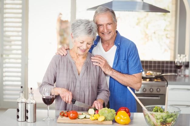 Vrolijk hoger paar dat een salade voorbereidt