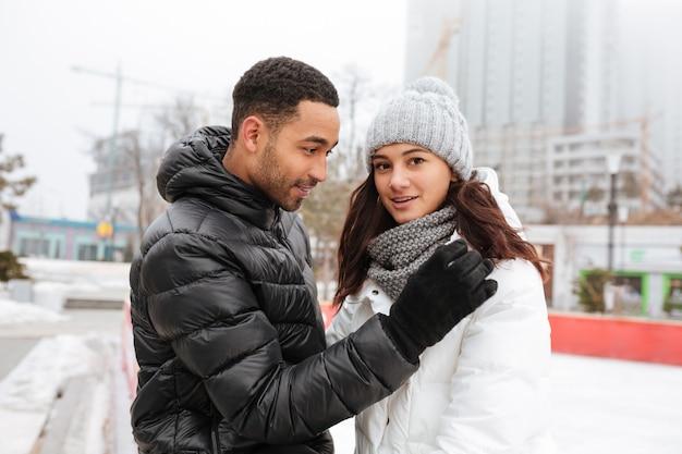 Vrolijk houdend van paar die bij ijsbaan in openlucht schaatsen.