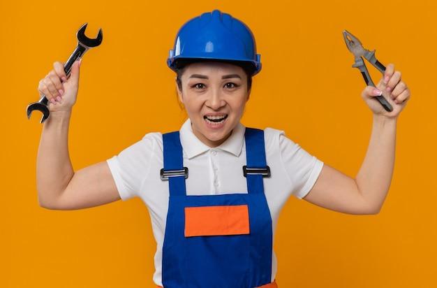 Vrolijk jong aziatisch bouwersmeisje met blauwe veiligheidshelm die tang en werkplaatssleutel houdt
