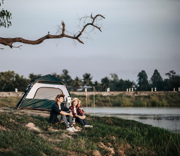Vrolijk jong backpackerpaar zit aan de voorkant van de tent in de buurt van het meer met koffieset en maakt verse koffiemolen tijdens het kamperen op zomervakantie