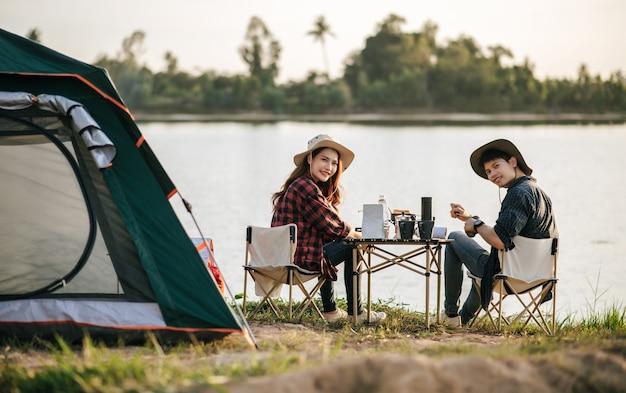 Vrolijk jong backpackerpaar zit aan de voorkant van de tent in het bos met koffieset en het maken van verse koffiemolen tijdens het kamperen op zomervakantie