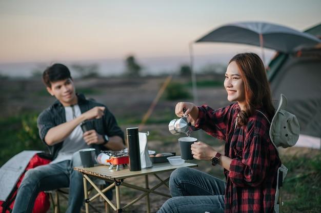 Vrolijk jong backpackerpaar zit aan de voorkant van de tent in het bos met koffieset en maakt verse koffiemolen tijdens het kamperen op zomervakantie, selectieve focus