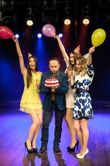 Vrolijk jong bedrijf viert verjaardag in een nachtclub.