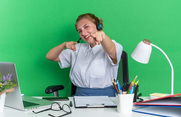 Vrolijk jong blond callcentermeisje met een headset die aan het bureau zit met werktuigen die je gebaren maken
