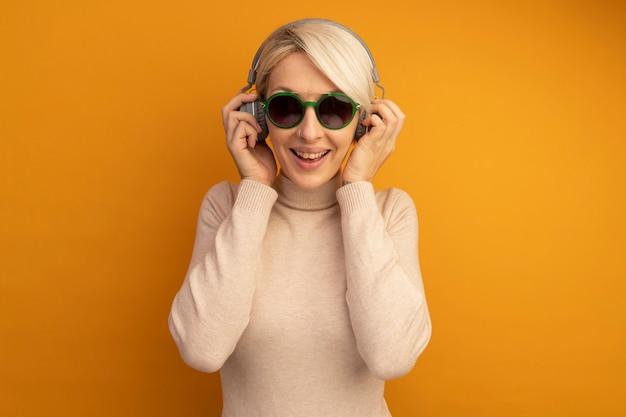 Vrolijk jong blond meisje met een zonnebril en een koptelefoon die een koptelefoon grijpt die naar muziek luistert die op een oranje muur is geïsoleerd met kopieerruimte