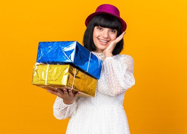 Vrolijk jong feestmeisje met een feesthoed met cadeaupakketten die de hand op het gezicht houden geïsoleerd op een oranje muur met kopieerruimte