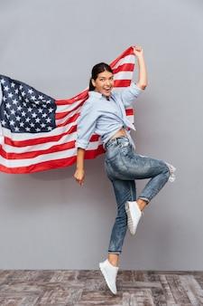 Vrolijk jong gelukkig meisje dat de vlag van de v.s. vasthoudt en over grijze muur springt
