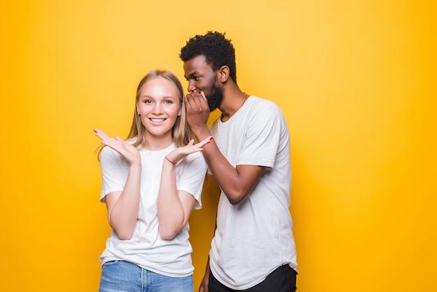 Vrolijk jong gemengd stel fluistert geheim achter haar hand en deelt nieuws poseren geïsoleerd op gele muur