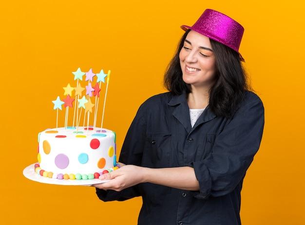 Vrolijk jong kaukasisch feestmeisje met een feesthoed die cake uitrekt met sterren die ernaar kijken, geïsoleerd op een oranje muur