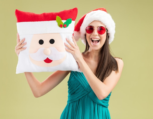 Vrolijk jong kaukasisch meisje in zonnebril met kerstmuts bedrijf santa kussen geïsoleerd op olijfgroene achtergrond met kopie ruimte