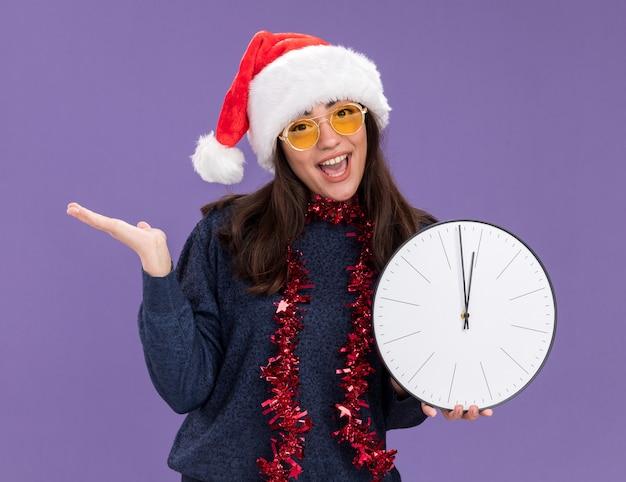 Vrolijk jong kaukasisch meisje in zonnebril met kerstmuts en slinger om de nek houdt de klok vast en houdt de hand open geïsoleerd op de paarse muur met kopieerruimte