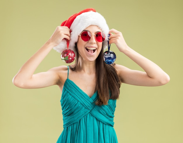 Vrolijk jong kaukasisch meisje in zonnebril met kerstmuts met glazen bolornamenten geïsoleerd op olijfgroene muur met kopieerruimte