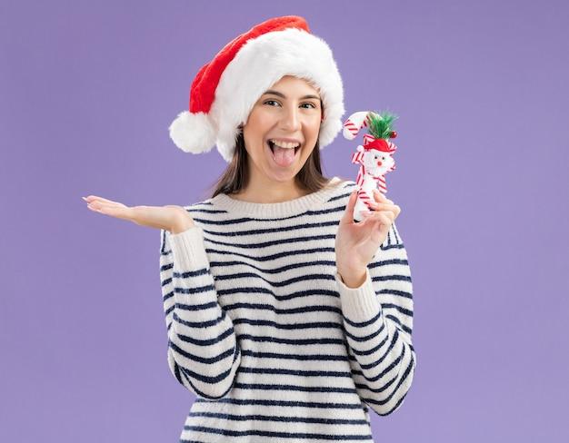 Vrolijk jong kaukasisch meisje met kerstmuts houdt snoepgoed vast en houdt hand open geïsoleerd op paarse muur met kopieerruimte