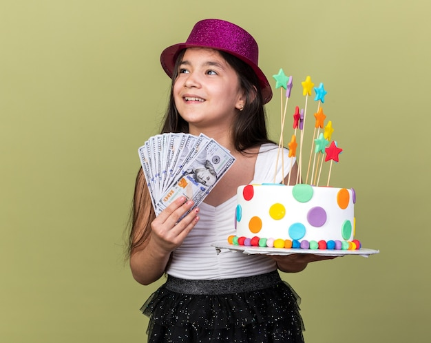 Vrolijk jong kaukasisch meisje met paarse feestmuts met verjaardagstaart en geld kijkend naar kant geïsoleerd op olijfgroene muur met kopieerruimte