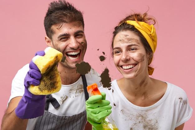 Vrolijk jong kaukasisch paar dat met vuile gezichten huis samen opruimt. glimlachend mooie vrouw en haar man, beide in beschermende handschoenen, venster wassen met reinigingsspray en spons