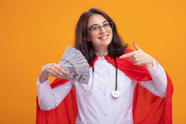 Vrolijk jong kaukasisch superheldenmeisje met doktersuniform en stethoscoop met een bril die vasthoudt en wijst naar geld geïsoleerd op de muur