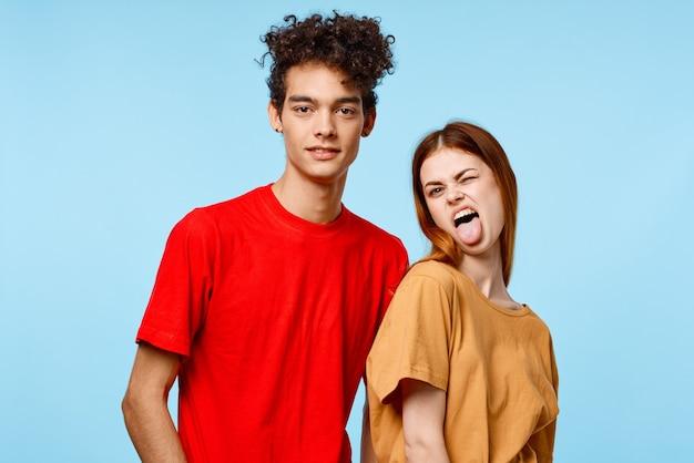 Vrolijk jong koppel in veelkleurige t-shirts communicatie studio blauwe achtergrond. hoge kwaliteit foto
