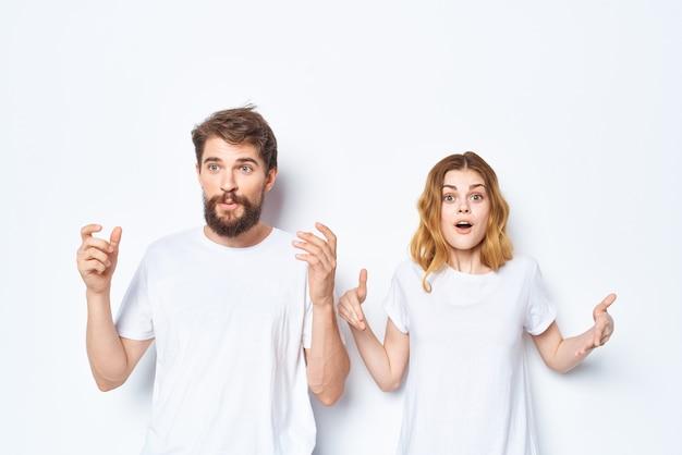 Vrolijk jong koppel in witte t-shirts en jeans studio poseren lichte achtergrond