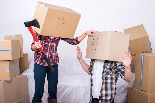 Vrolijk jong koppel met kartonnen dozen op hun hoofd.