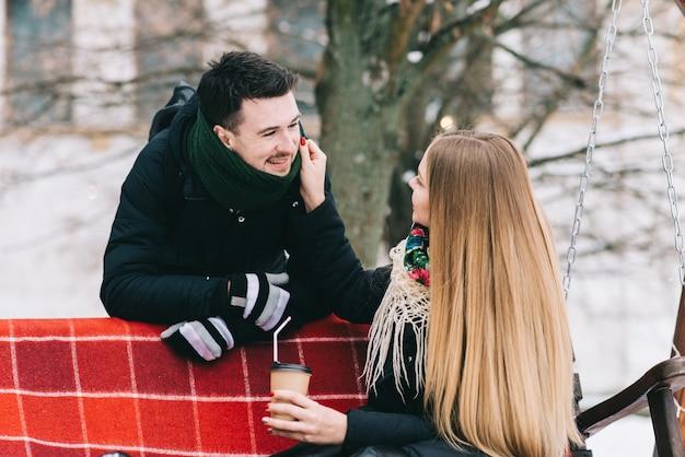 Vrolijk jong liefdevol stel drinkt koffie in de winter buiten. ze glimlachen en kijken naar elkaar terwijl ze een romantische date hebben