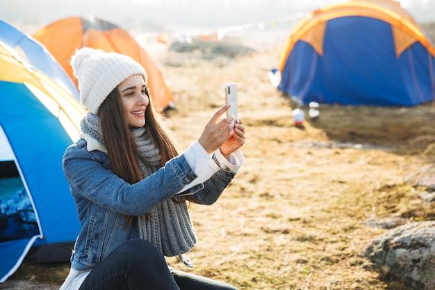 Vrolijk jong meisje dat buiten op de camping zit, mobiele telefoon gebruikt, een selfie maakt