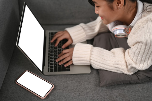 Vrolijk jong meisje dat op bank ligt en computerlaptop gebruikt.