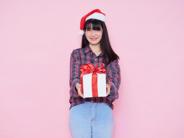 Vrolijk jong meisje dat santahoed draagt die geïsoleerde giftdoos geeft