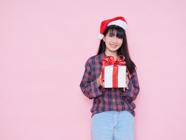 Vrolijk jong meisje dat santahoed met de doos van de holdingsgift draagt