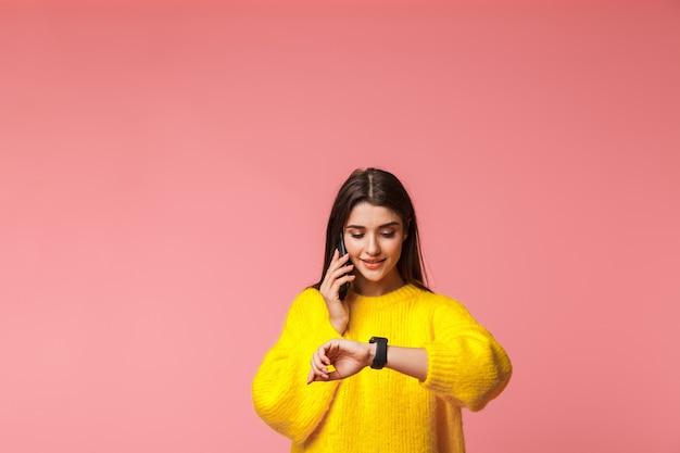 Vrolijk jong meisje dat trui draagt die zich geïsoleerd over roze bevindt, die op mobiele telefoon spreekt, de tijd controleert