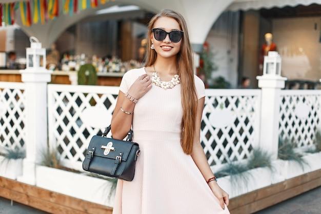 Vrolijk jong meisje in een roze jurk met handtas heeft plezier