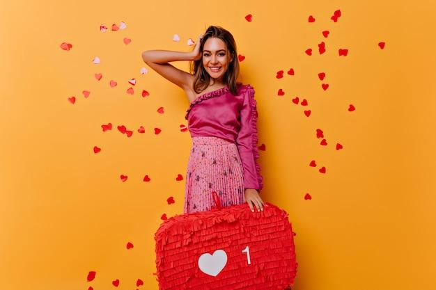 Vrolijk jong meisje in roze jurk genieten van sociale netwerken. portret van schattige dame geluk uitdrukken op geel.